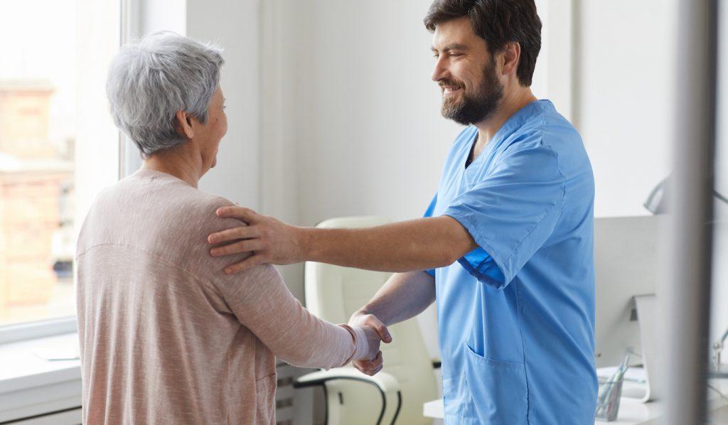 Metge saludant al seu pacient