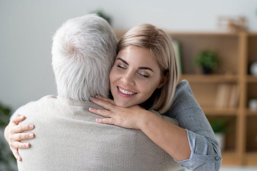 Dona jove i afectuosa feliç amb un somriure de dents abraçant el seu pare gran