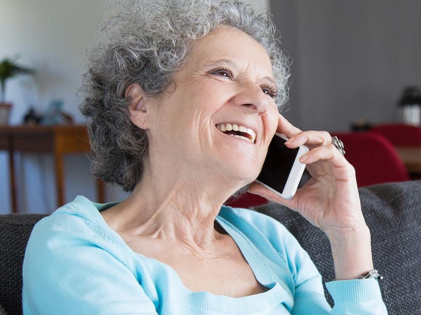Retrat de l'� via feliç asseguda al sof� i parlant per telèfon