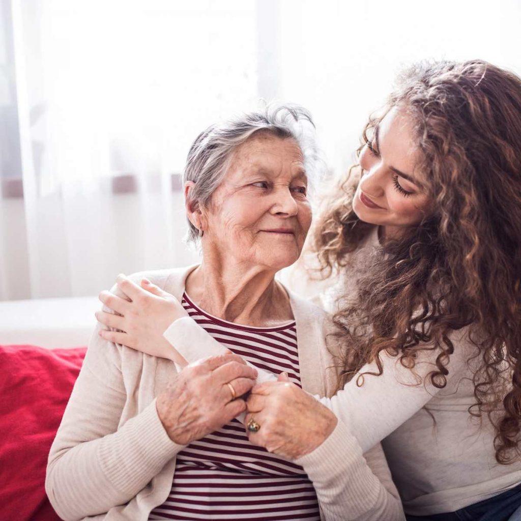 Mujer joven y cariñosa feliz y sonrisa abrazando una anciana